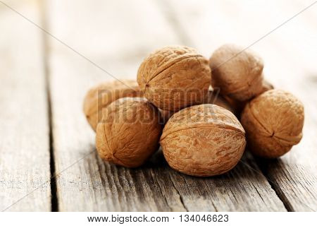 Walnuts on a grey wooden table, close up