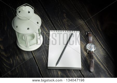 Lamp notebook and a watch on a wooden background