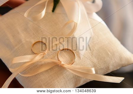 two wedding rings on a cushion tied with ribbon.