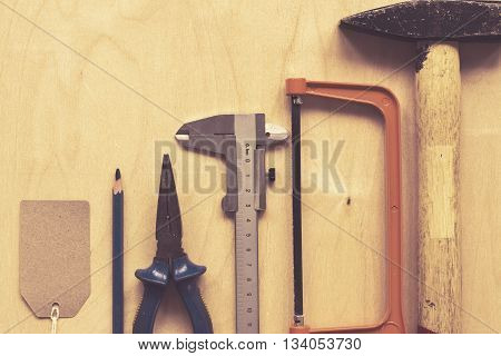 Assortment of tools over plywood background. Fathers day concept. Top view, space for text. Toned image