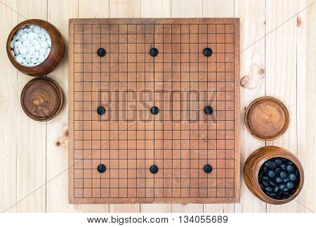 top view two wooden bowls filled black and white stones with nine handicap stones on go game board over wooden table traditional chinese strategy board game sport hobby and recreation