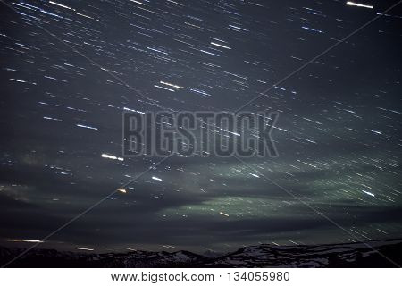 Beautiful night landscape with traces of stars in the night sky and clouds on a background of mountains covered with snow shot with a long exposure