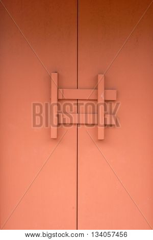 Simple red wooden door with latch. Thai architecture and culture concept.