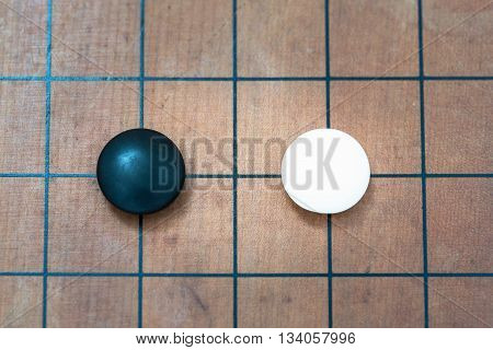 top view closeup white stone approach to black stone on go game board traditional chinese strategy board game sport hobby and recreation