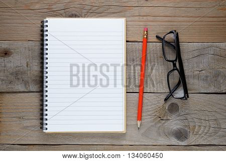 Notepad pencil and glasses on old wooden table top view