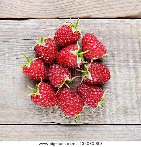 Ripe raspberries on wooden table top view