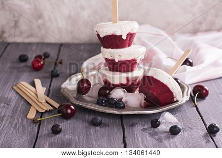 Delicious homemade black forest popsicles with cherry and blueberry