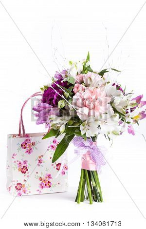 Pastel bouquet from pink and purple gillyflowers and alstroemeria on white background with gift