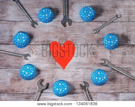 Father's day background on rustic wooden board with wrenches and blue muffin papper cases with stars and a red paper heart