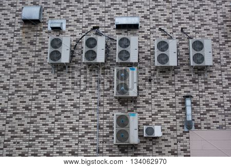 A lot of air conditioners placed on the brick wall without windows