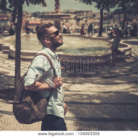 Handsome tourist with backpack and sunglasses is walking across old city.
