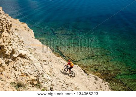 Mountain biker riding a bike at the seaside and mountains landscape. Man cycling MTB on enduro trail dirt path. Sport fitness motivation and inspiration in beautiful environment.