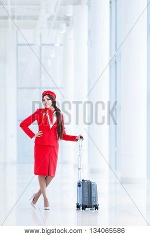 Smiling stewardess with luggage