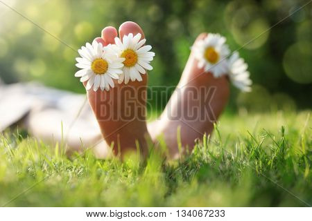 Child with daisy between toes lying in meadow relaxing in summer sunshine