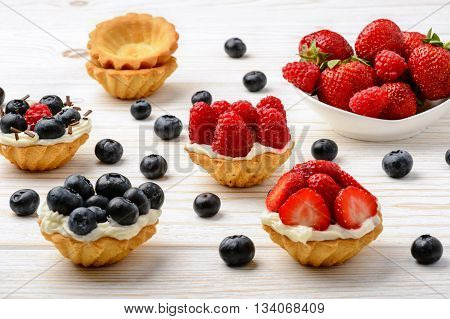 Tartlets with cream, blueberries, raspberries and strawberries on white wooden table.