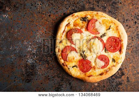 Pizza Margherita with tomatoes and mozzarella cheese on a rust effect surface