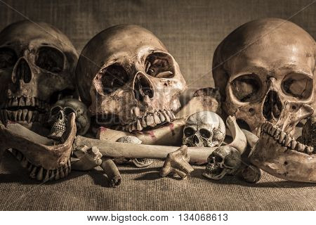 still life photography with closeup pile of skulls and animal bones on sackcloth background. Genocides concept horror creepy halloween background
