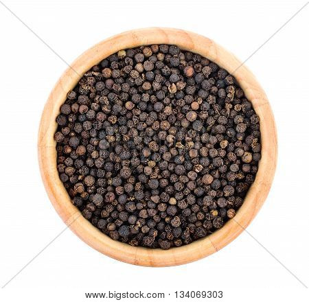 peppercorns in wood bowl isolated on white background