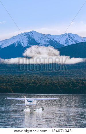 water plane floating over fresh water lake against beautiful mountain scenery in lake te anau new zealand