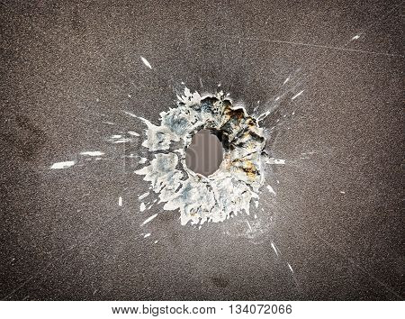 Bullet hole in the metal plate. Weapons theme. Armed conflict. Symbolic object. Detail of shot.