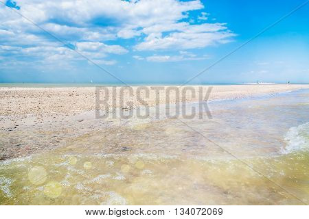 Sand spit on the sea on a summer morning on a background of blue sky with clouds flecks of sunlight