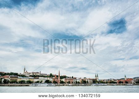 Skyline of waterfront in Budapest Hungary. Travel destination. Matthias church Fishermans bastion and Calvinist church. Danube river and cloudy sky. Cultural heritage. Architectural theme.