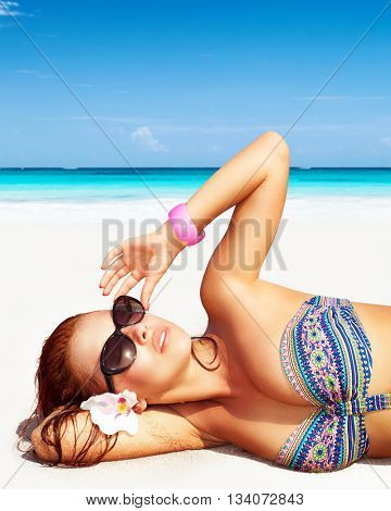Portrait of a pretty woman on the beach, wearing sunglasses, lying down on clean white sandy coast, enjoying day spa on a tropical resort, luxury summer vacation