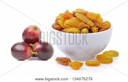 Golden raisins in the white bowl with red grapes on white background
