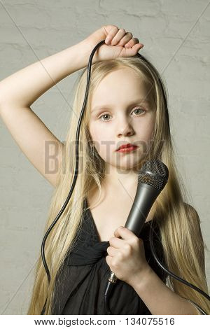 Pretty blond girl with microphone on grey background