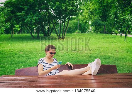 Young woman using a smartphone in nature sitting on the table