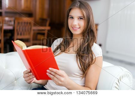 Portrait of a woman reading a book while relaxing on the couch