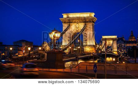 Ancient chain bridge on danube river in budapest city with lanterns for nighttime backlighting and blue sky