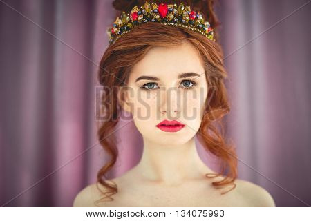 Beautiful redhaired fashion model posing in evening dress and in the diadem over dark background