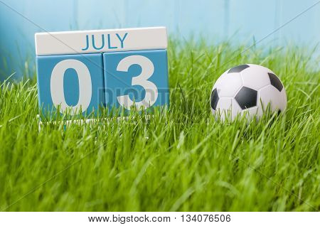 July 3rd. Image of july 3 wooden color calendar on green lawn grass background. Summer day.
