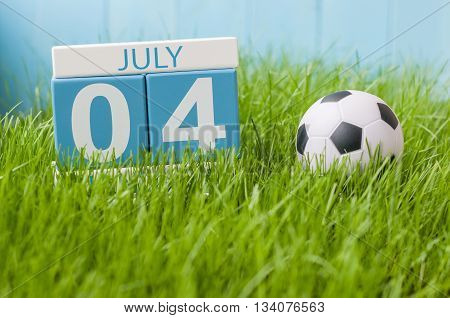 July 4th. Image of july 4 wooden color calendar on green lawn grass background. Summer day.