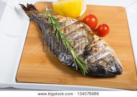 Whole grilled dorado fish on wooden board plate