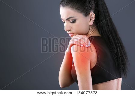 Body pain. Studio shot of beautiful young woman with dark brown hair. Woman suffering from shoulder pain. Red spot on shoulder