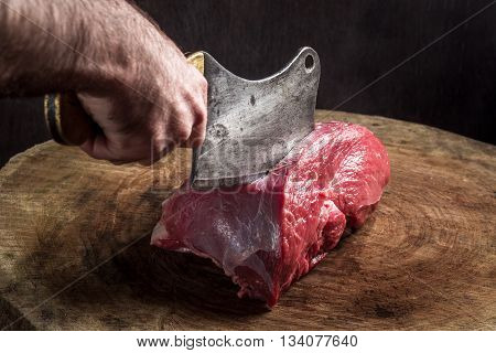 butcher cuts meat. old hatchet and impressive wooden base