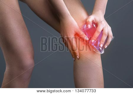 Body pain. Close up studio shot of woman. Woman suffering from knee pain. Red spot on knee. Woman holding freezing gel on knee