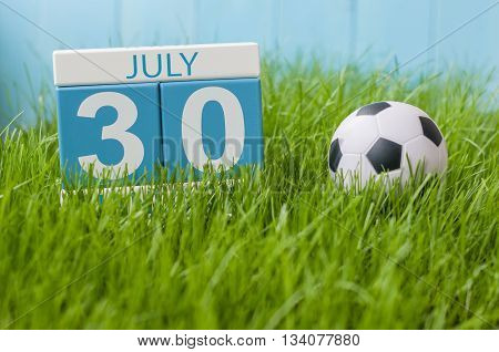 July 30th. Image of july 30 wooden color calendar on greengrass lawn background. Summer day, empty space for text.