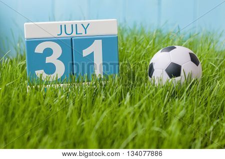 July 31st. Image of july 31 wooden color calendar on greengrass lawn background. Summer day, empty space for text.