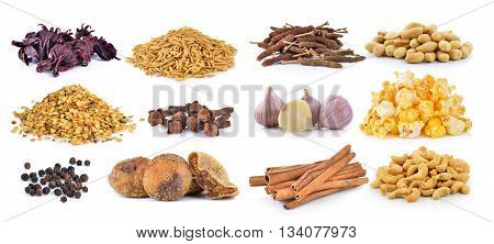 Dried figs, pepper corn, chili seeds, spice cloves, rice grains, Dried okra, cashew nuts, peanuts, garlic, popcorn and cinnamon on a white background