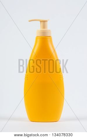 Yellow plastic bottle with cream soap isolated on white background . Studio shooting.