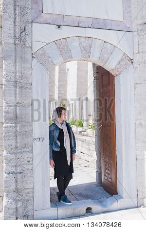 woman in a denim jacket and a scarf standing under an arch of stone wall