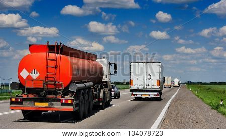 A highway with trucks, tank trucks. Against the background of the blue, cloudy sky