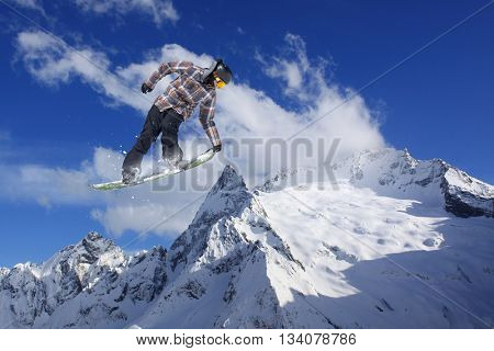 Snowboard rider jumping on mountains. Extreme freeride sport.