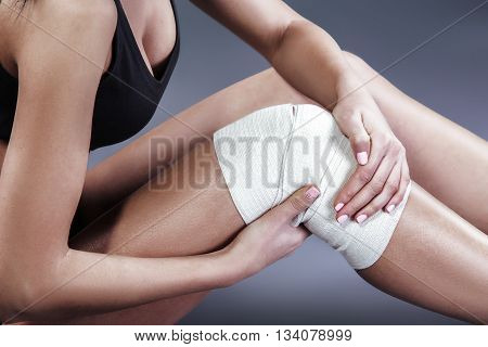 Body pain. Close up studio shot of woman. Woman suffering from knee pain. Woman with elastic bandage on knee