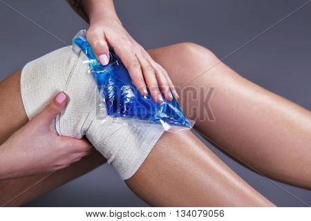 Body pain. Close up studio shot of woman. Woman suffering from knee pain. Woman with elastic bandage and freezing gel on knee