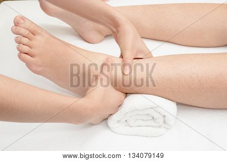 Foot massage therapist's hands massaging female foot