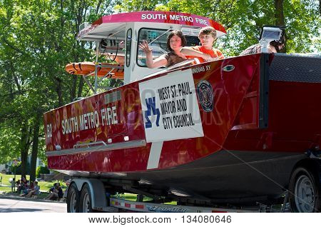 WEST ST. PAUL, MINNESOTA - MAY 21, 2016: Annual West St. Paul Days Grande Parade led by South Metro Fire automobile with water rescue boat traveling up Smith Avenue in West St. Paul on May 21.